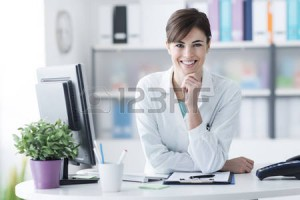 52945558-attractive-young-female-doctor-leaning-on-the-clinic-reception-desk-with-hand-on-chin-she-is-smiling
